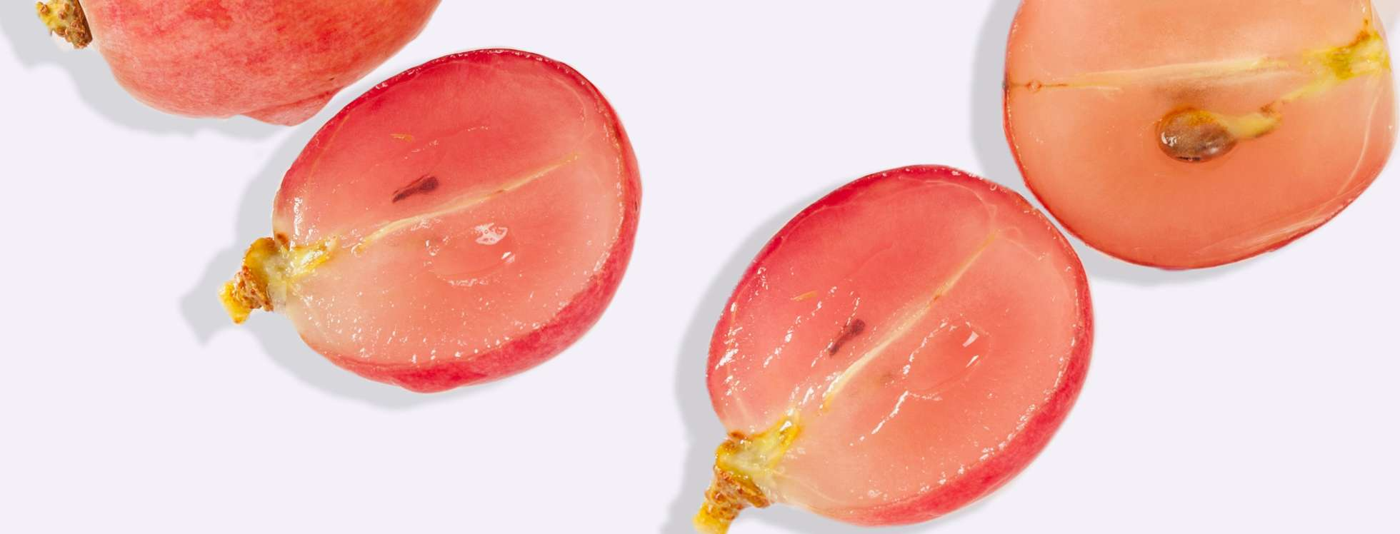 Cross section of pink grape on grey background