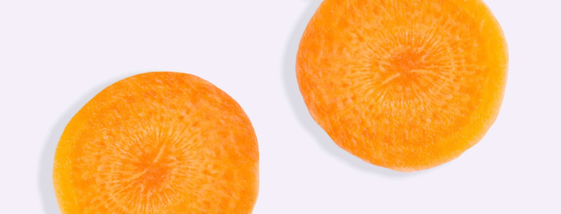 Cross section of orange carrot on grey background