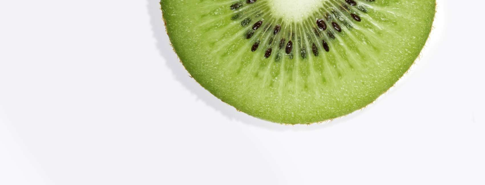 Cross section of kiwi fruit on grey background