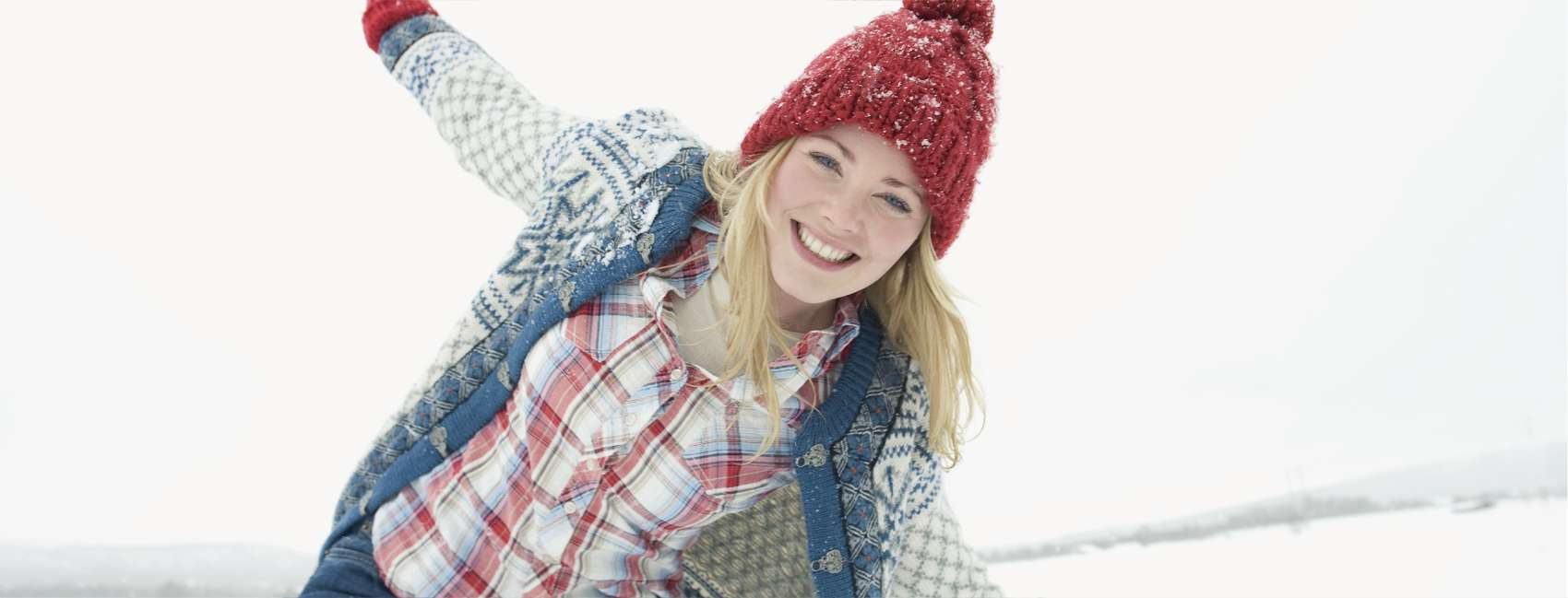 Smiling blonde girl wearing red beanie playing in the snow