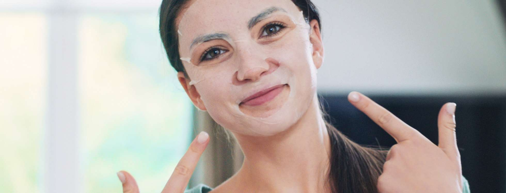 Smiling girl wearing a sheet mask pointing at her face