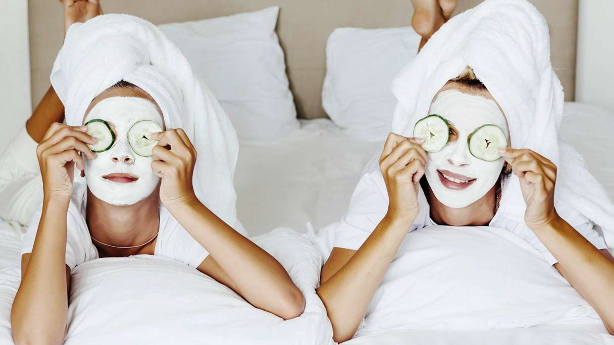 Two girls lying on a bed wearing face masks and holding cucumbers over their eyes