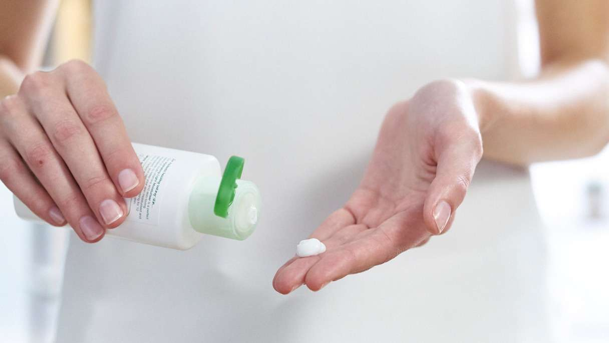 Woman squeezing Simple moisturiser into her hand