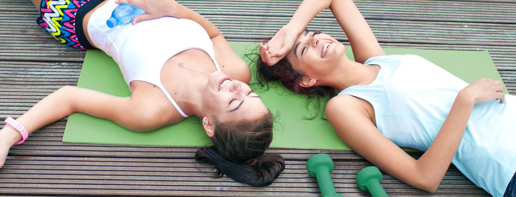 Two smiling girls lying on an exercise mat