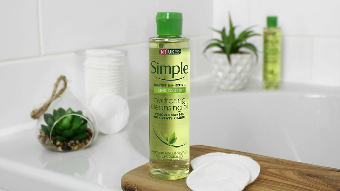 A bottle of Simple Hydrating Cleansing Oil in a bathroom setting