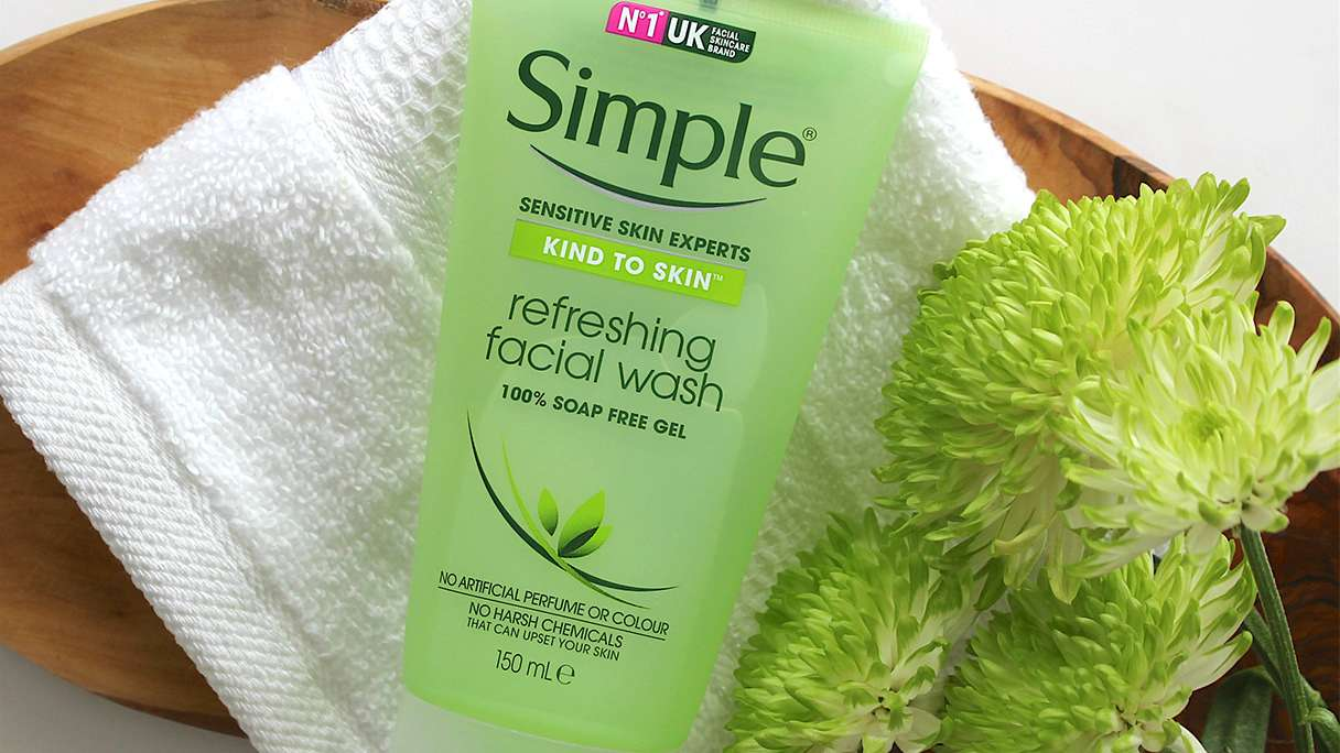 Tube of Simple Refreshing Facial Wash lying on a white face cloth alongside green flowers