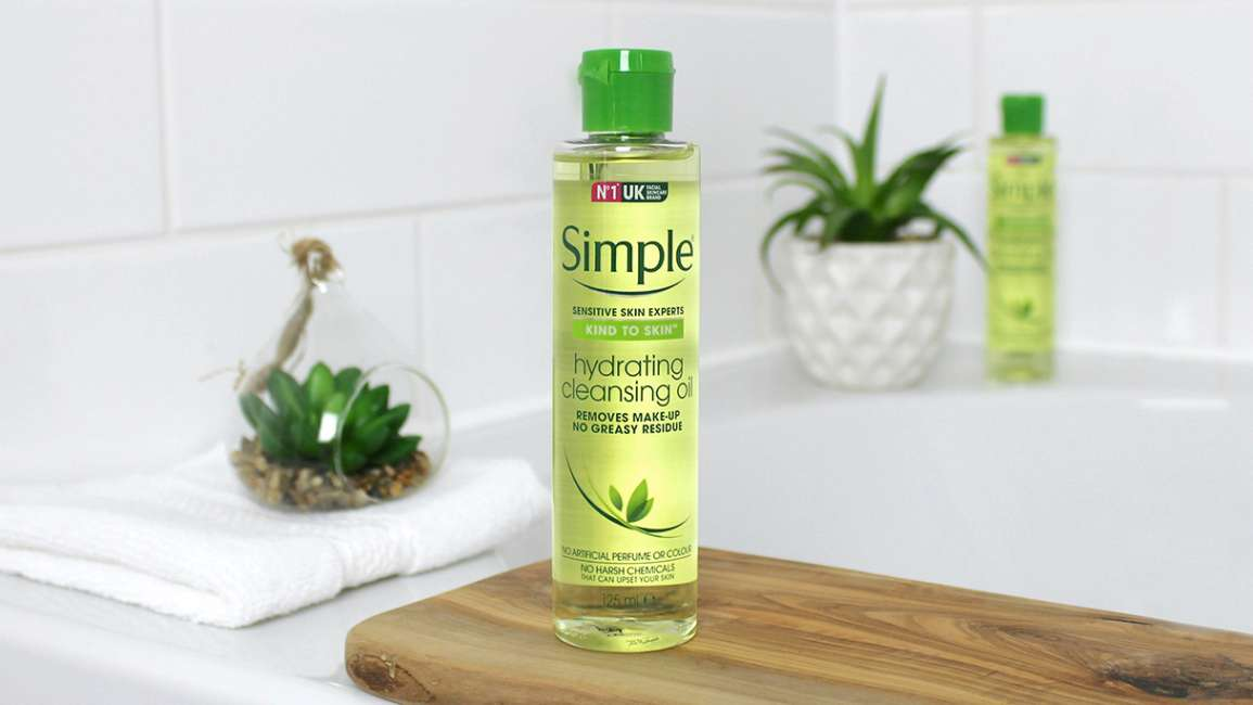 Bottle of Simple Hydrating Cleansing Oil with cotton pads in a bathroom setting