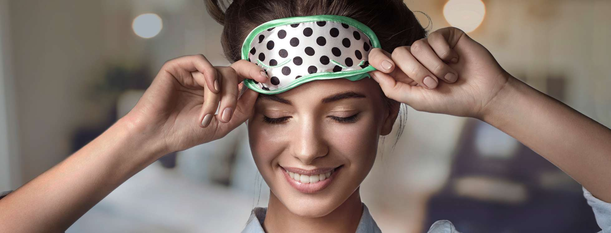 Smiling girl removing a spotty eye mask