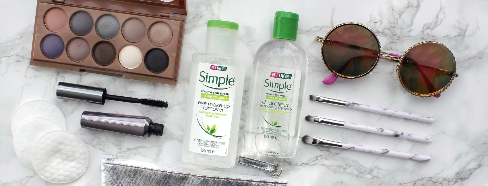 Flat lay Simple Eye Make-up Remover products with coloured eyeshadows, make-up brushes and mascara on marble countertop.