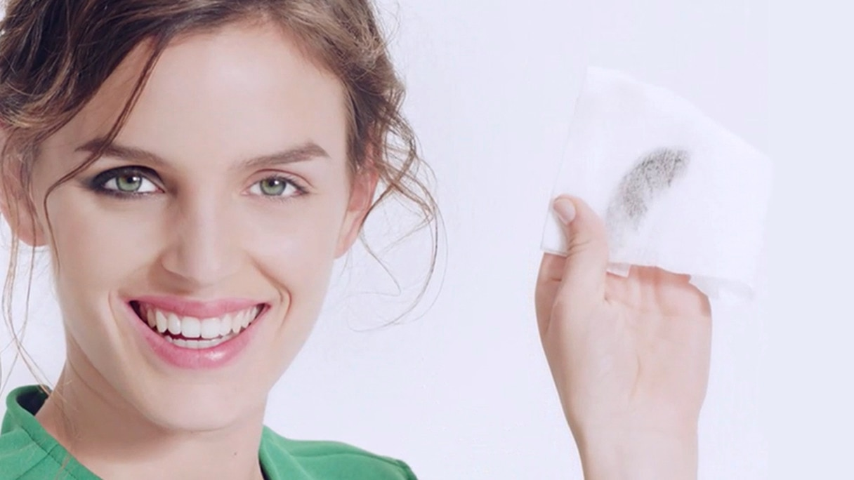Smiling woman removing eye make-up with cotton pad.