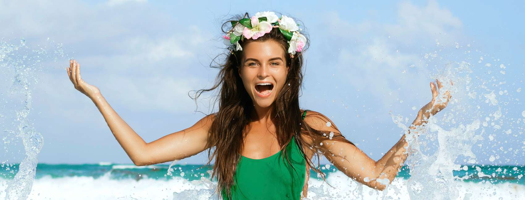 Smiling girl wearing a green top and flower crown, splashing around in the sea