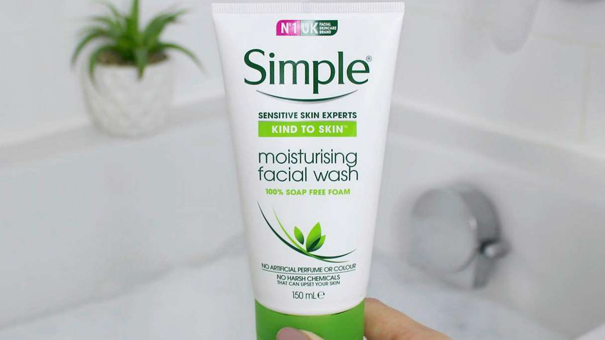 Hand holding a tube of Simple Moisturising Facial Wash with a bath and plant in the background