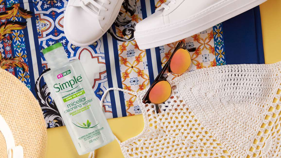 Flatlay of Simple Micellar Cleansing Water with sneakers, hat and sunglasses
