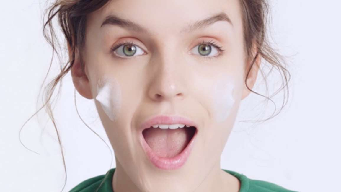 Smiling woman with moisturising cleanser on her cheeks