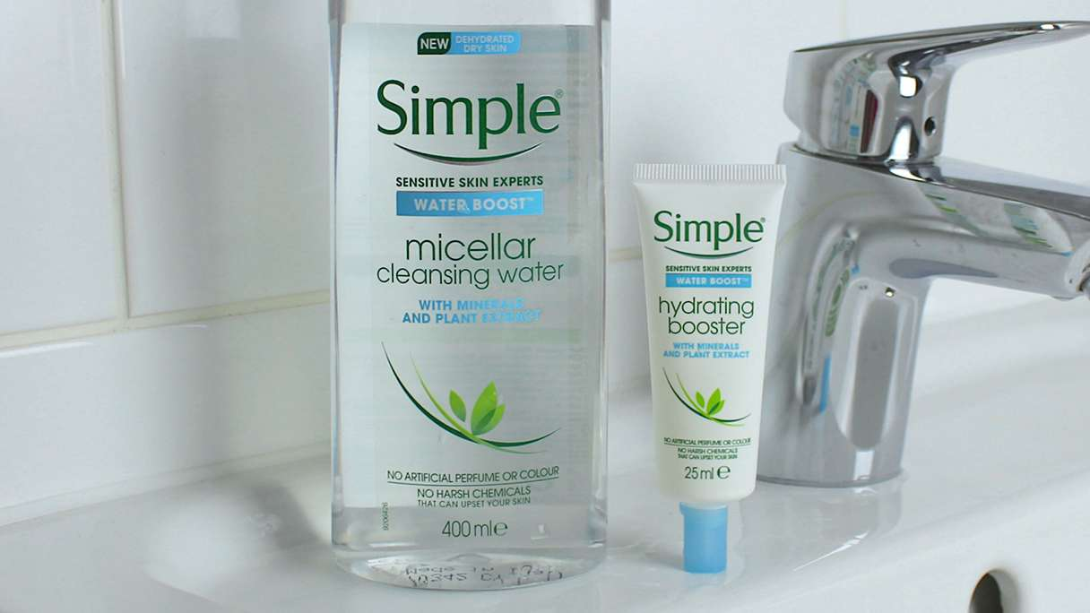 Simple Water Boost Micellar Cleansing Water on a counter alongside make-up brushes, cotton pads and a magazine.