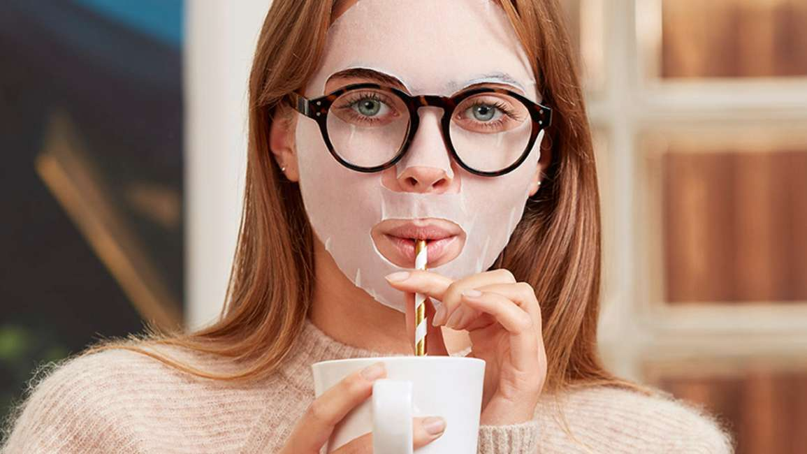 Girl wearing a sheet mask and spectacles sipping a drink through a straw