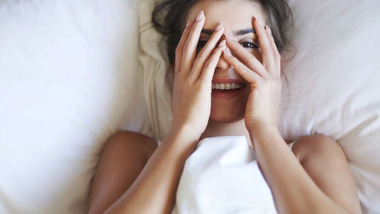 Woman in bed covering her eyes with her fingertips