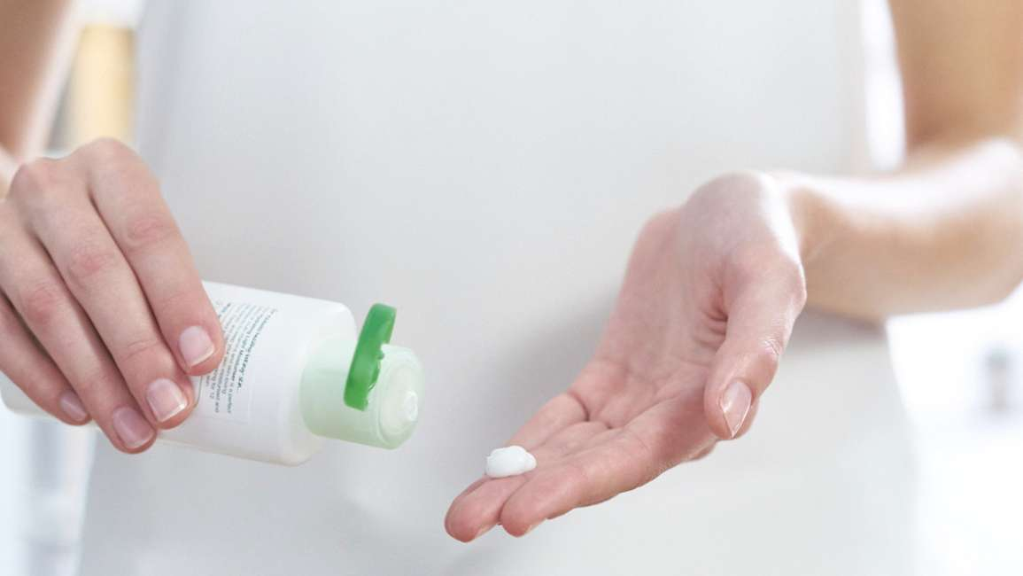 Woman squeezing Simple moisturiser onto her fingertips