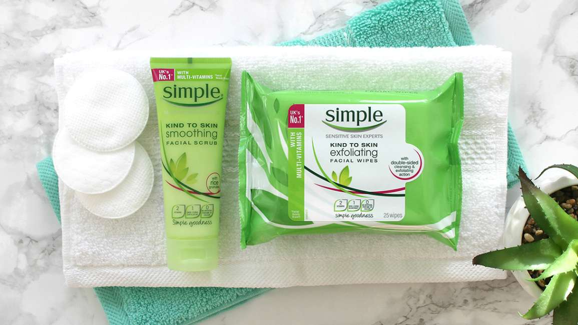 Simple Soothing Facial Scrub and Exfoliating Wipes lying flat on folded green and white face cloths