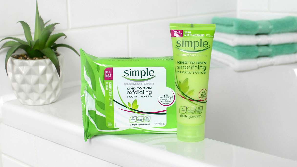 Simple Soothing Facial Scrub and Exfoliating Facial Wipes sitting on the edge of a bath