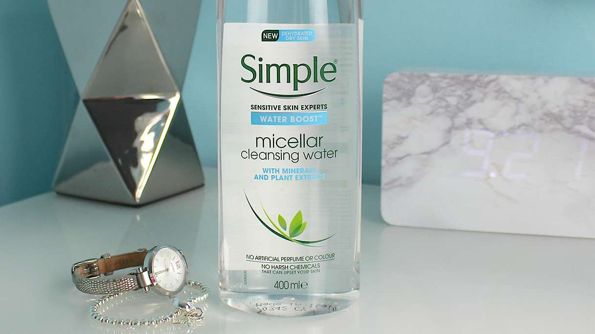 Simple Water Boost Micellar Cleansing Water on bedside table with lamp in the background