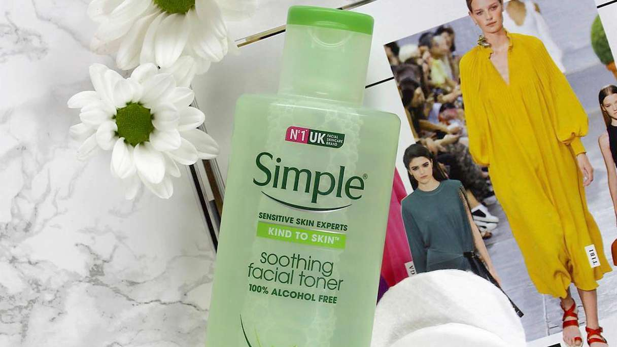 A bottle of Simple Soothing Facial Toner lying on a magazine with cotton pads in the background