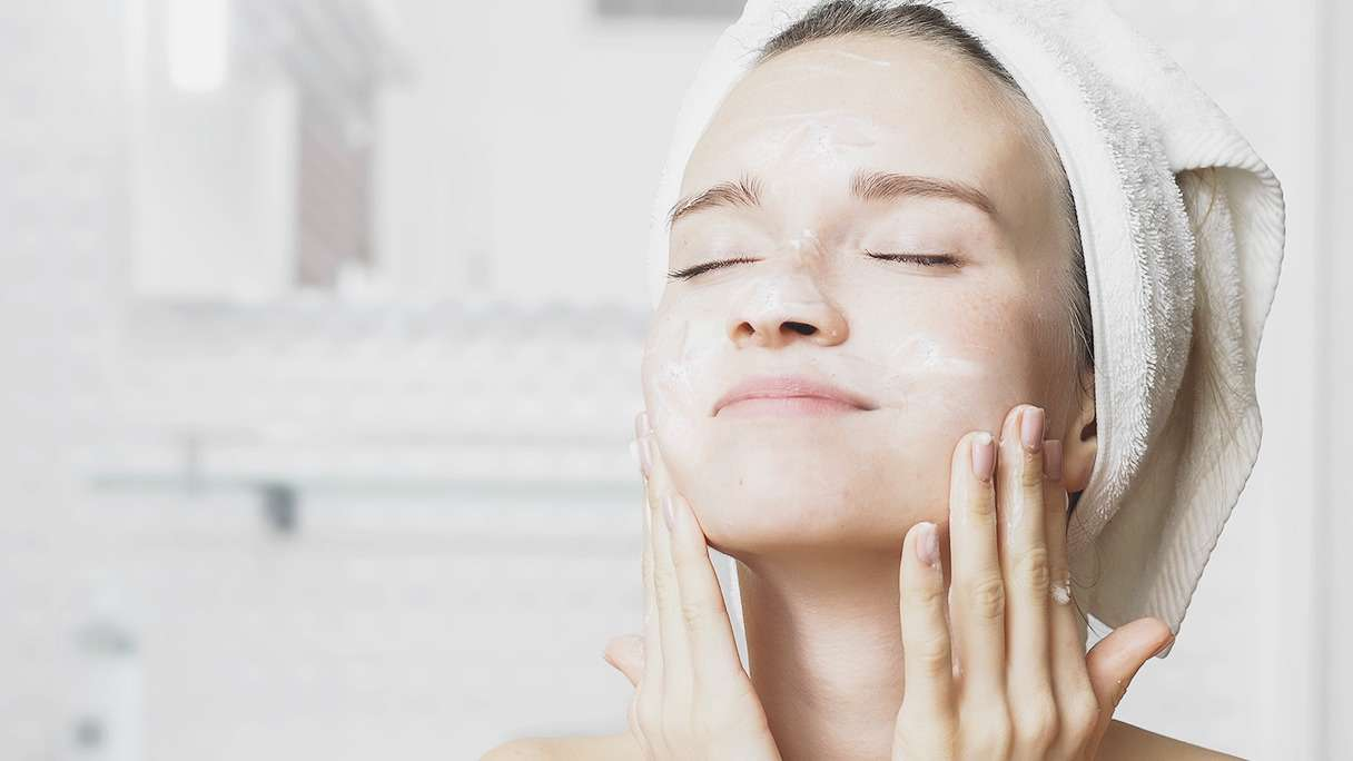 Girl with closed eyes rubbing cleanser on her face wearing a towel on her head