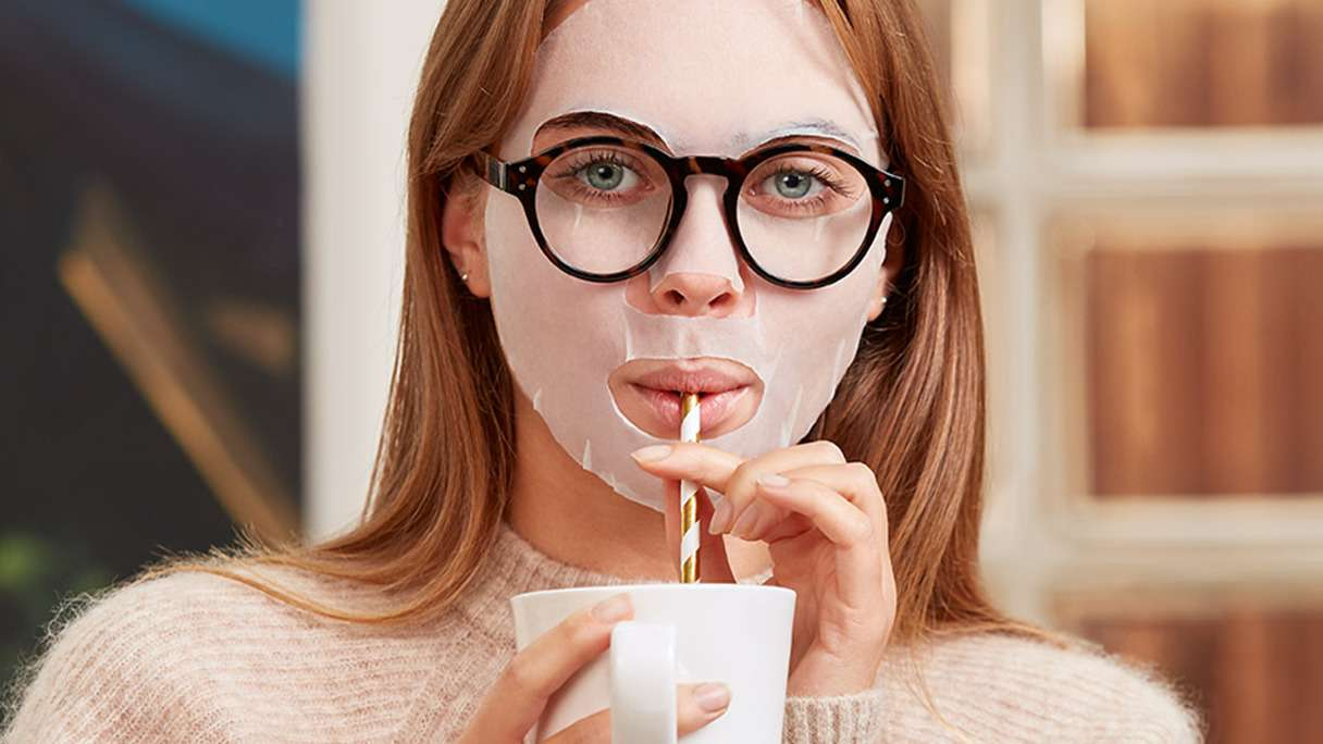 Girl wearing a sheet mask and spectacles while sipping a drink through a straw