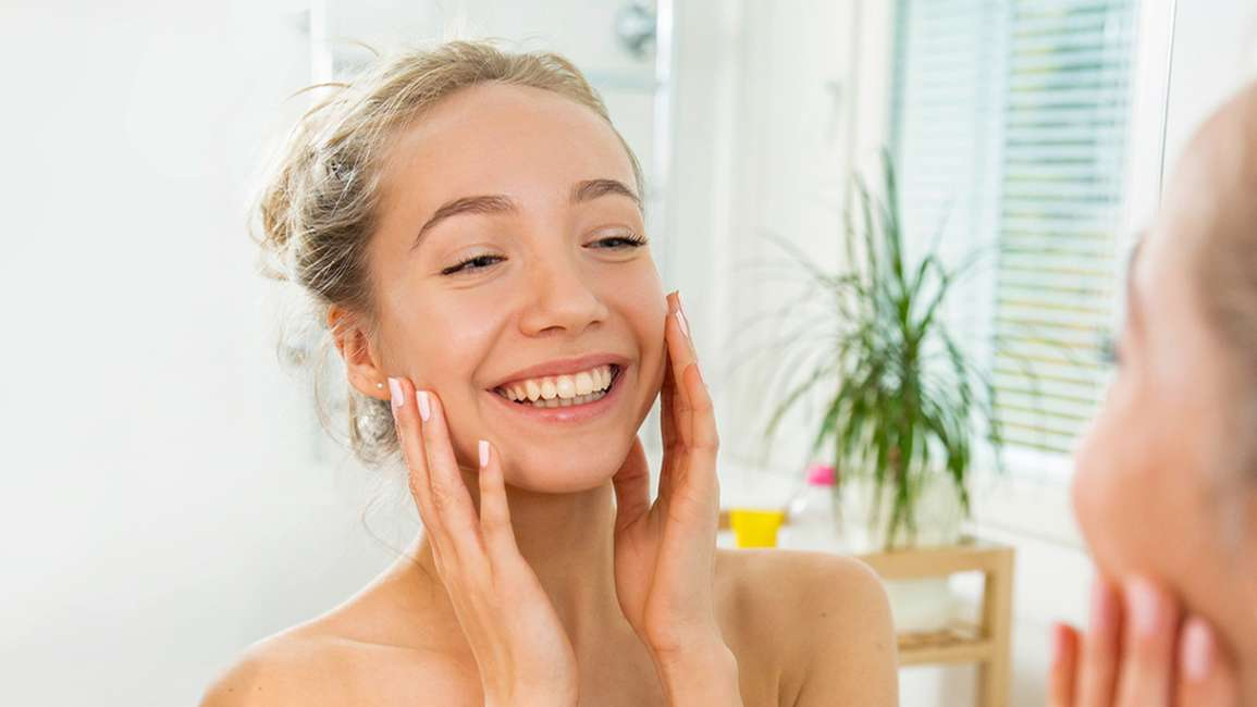 A smiling woman cleansing her face in the bathroom mirror