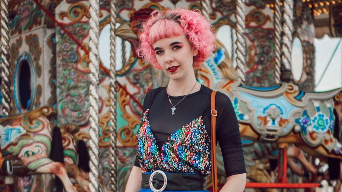 Young woman with pink hair wearing vintage clothes in front of a fairground ride