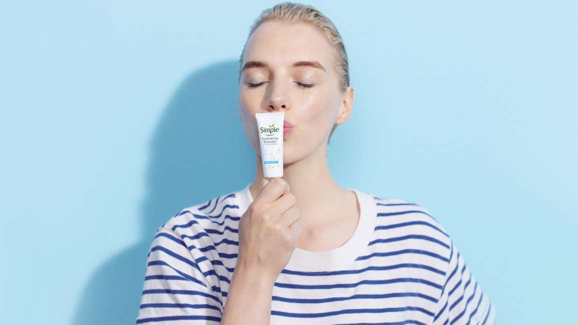 A woman in striped top kissing Simple hydrating booster tube against a blue background