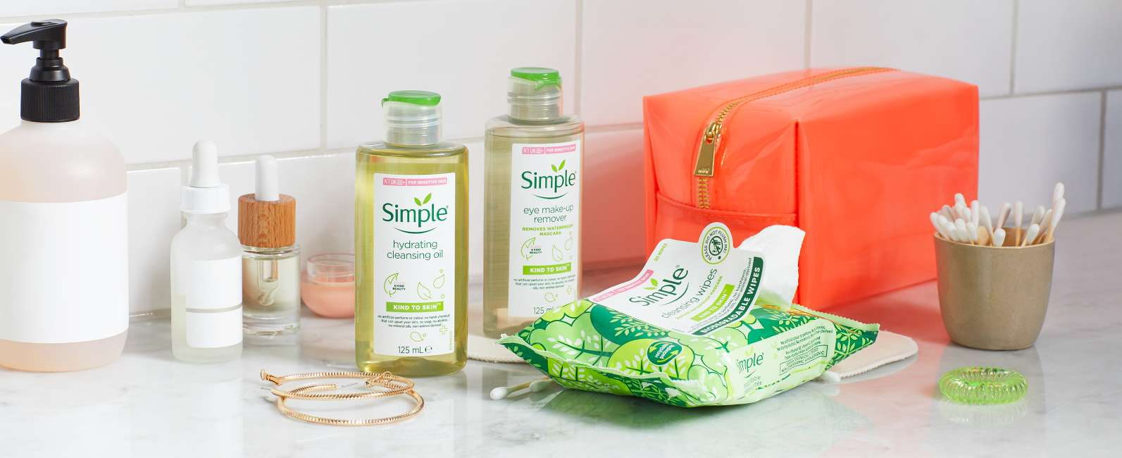 Simple products with cotton buds and toiletry bag and on a white bathroom shelf