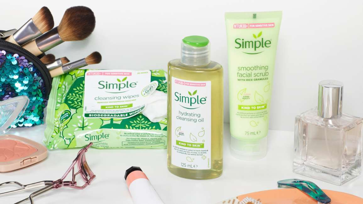 Simple Facial Cleansing Oil, facial wipes, face scrub and make up bag with brushes on table