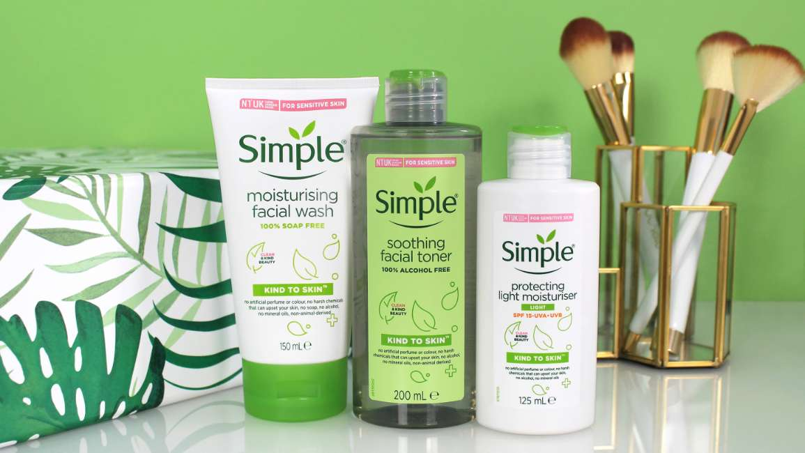 A selection of Simple products with makeup brushes against a green background