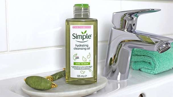 Bottle of Simple Hydrating Cleansing Oil alongside cotton pads in a bathroom setting