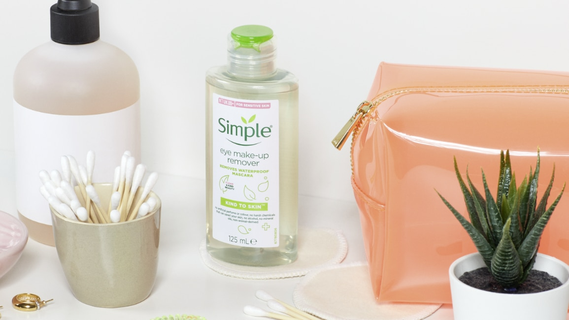 Styled shot of Simple Eye makeup remover with toiletry bag, cotton buds on white bathroom shelfm