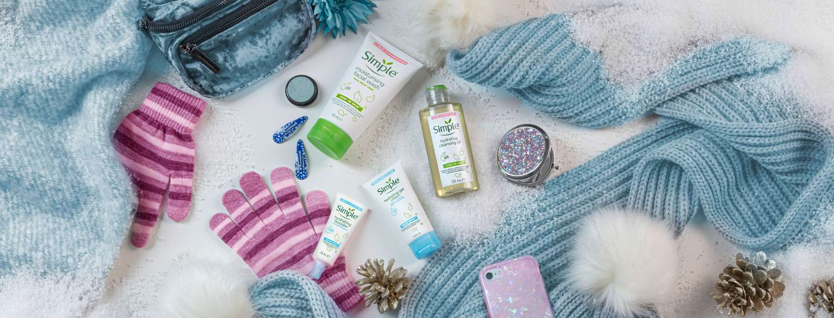 Flat lay of Simple skincare products on a fluffy white background with a beanie and gloves